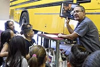 A bus driver giving a group of students a tour of the bus garage.
